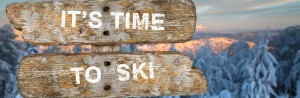 "Wegweiser ""It's time to ski"" in verschneiter Berglandschaft"